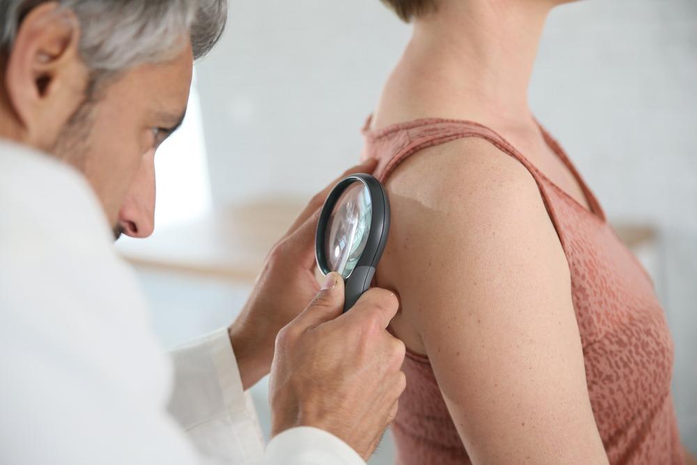Dermatologista observa pele do paciente
